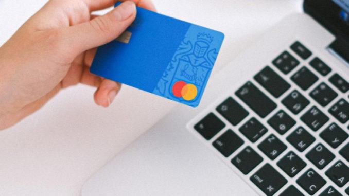 Homme qui tient carte bancaire devant un ordinateur
